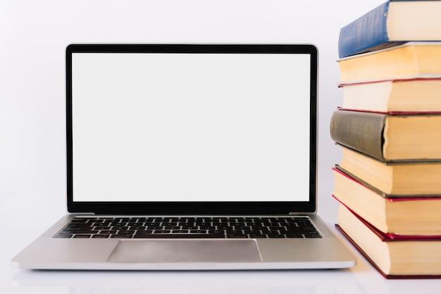 Laptot à côté de la pile de livres