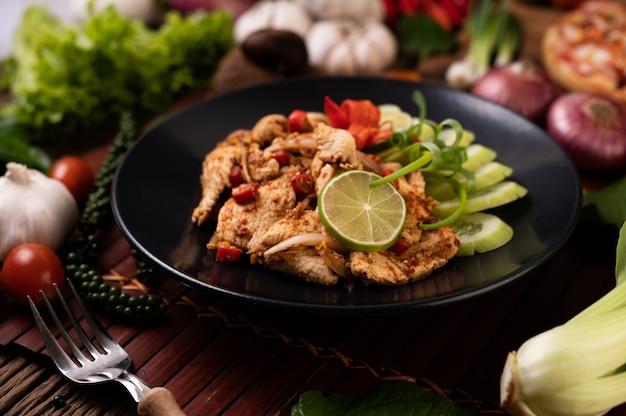 Larb de poulet dans l'assiette avec piments séchés, tomates, oignons nouveaux et laitue