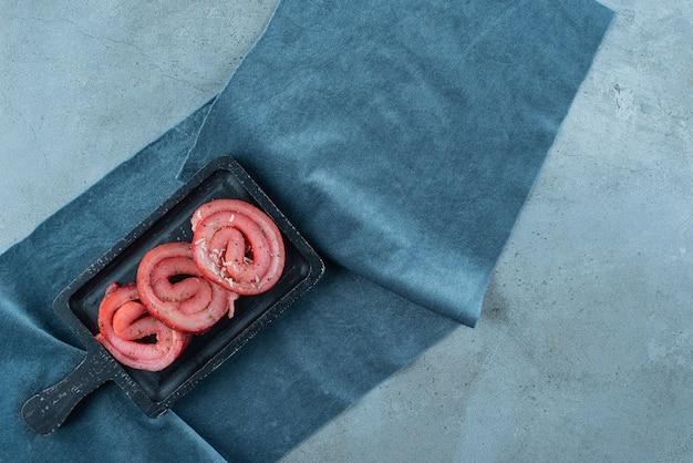 Lard de porc sur une planche sur des morceaux de tissu, sur la table bleue.
