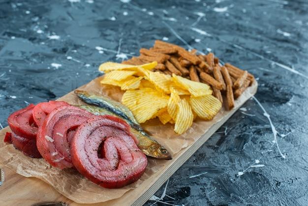 Lard de porc, poisson, frites et chapelure sur une planche à découper , sur la table bleue.