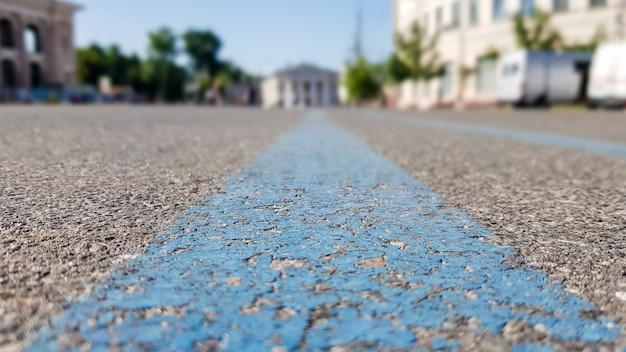 Une large bande bleue sur une surface asphaltée noire. route goudronnée dans la ville, été, arbres verts, ciel bleu. vue en contre-plongée depuis les lignes bleues du milieu.