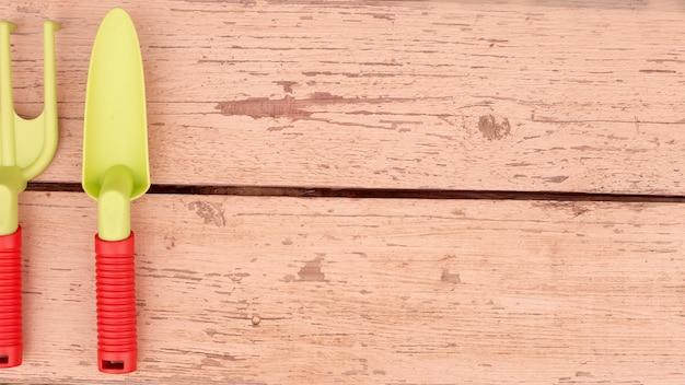 Large bannière avec des outils de jardinage à main. sur les planches peintes se trouvent une pelle et un râteau à l'orange