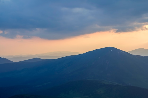 Large panorama, vue fantastique sur couvert de brume matinale des montagnes des carpates à l'aube sous des nuages sombres et un ciel rose clair avant le lever du soleil. beauté de la nature, du tourisme et du concept de voyage.
