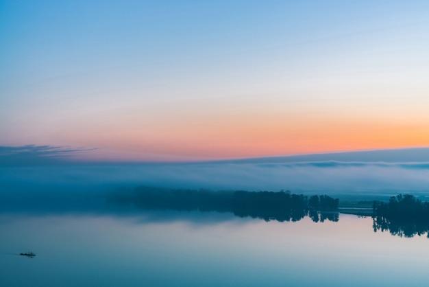Large rivière coule le long de la rive diagonale avec la silhouette de la forêt et un épais brouillard