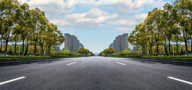 Large route goudronnée avec des bâtiments à l'horizon