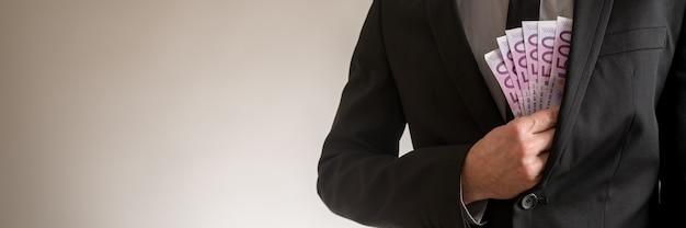 Large vue image d'un homme d'affaires mettant des billets de 500 euros dans sa poche de veste de costume élégante. avec espace de copie sur le côté gauche d'une image.