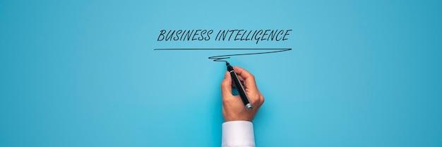 Large vue image de la main masculine écrit business intelligence signe avec marqueur noir sur fond bleu.