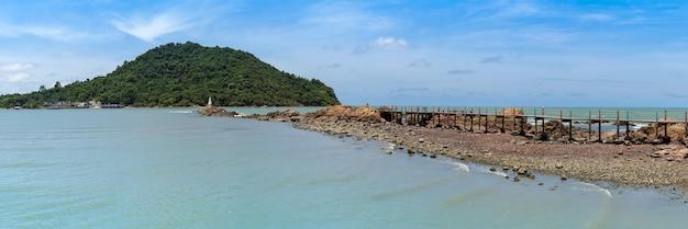 Large vue panoramique sur le paysage marin avec pont en bois jusqu'à la pagode blanche sur le rocher dans la mer bleue, la grande montagne et le ciel bleu avec des nuages, chedi ban hua laem, destination de voyage à chanthaburi, en thaïlande.