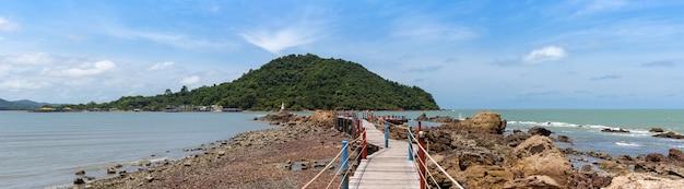 Large vue panoramique sur le pont en bois du paysage marin avec rail de corde jusqu'à la pagode blanche sur le rocher dans la mer bleue, la grande montagne et le ciel bleu avec des nuages, chedi ban hua laem, destination de voyage à chanthaburi, en thaïlande.