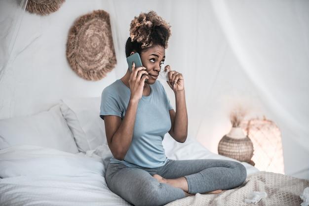 Des larmes, de l'émotion. jeune adulte femme afro-américaine parlant sur smartphone et tenant la serviette près des yeux à la maison sur le lit
