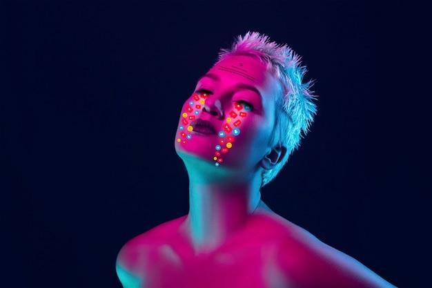 Larmes inspirées illustrées de signes d'activité sur les réseaux sociaux sur le visage d'une femme dans la vraie vie au néon