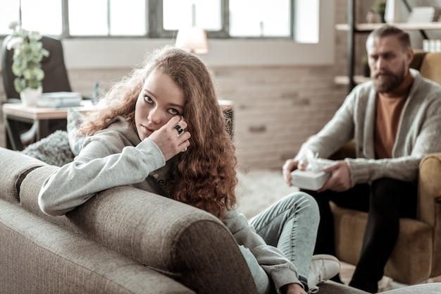 Larmes sèches. adolescente bouclée ayant une profonde dépression séchant ses larmes pendant une thérapie psychologique