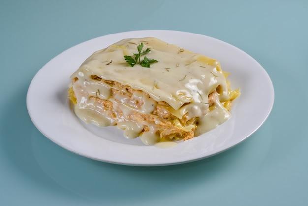Lasagne au poulet dans un plat blanc isolé sur fond neutre.