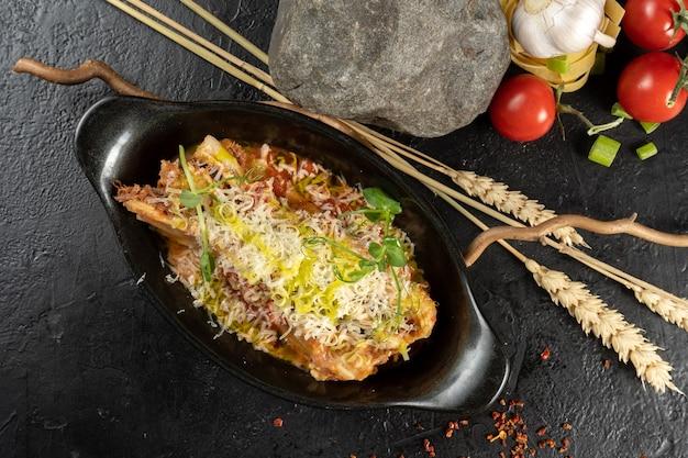Lasagne bolognaise. un plat principal chaud composé de pâtes, viande hachée, légumes, sauce béchamel et fromage