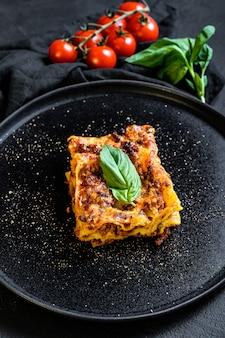 Lasagne italienne maison avec sauce tomate et boeuf. mur noir. vue de dessus