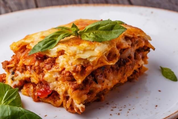 Lasagne traditionnelle à la sauce bolognaise de bœuf hachée et sauce béchamel garnie de feuilles de basilic.
