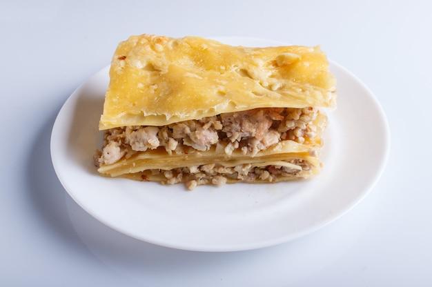 Lasagne à la viande hachée et au fromage isolé sur fond blanc.