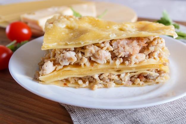 Lasagne à la viande hachée et au fromage sur une surface en bois brune.