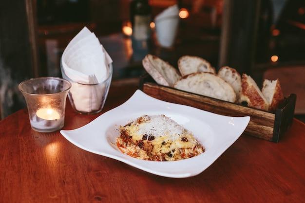 Lasagnes chaudes servies garnies de fromage mozzarella et de pain tranché dans une boîte en bois.