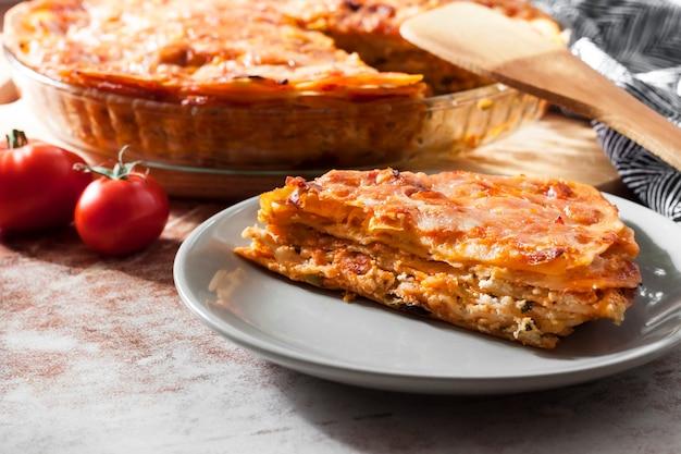 Lasagnes cuites au four dans un plat de cuisson en verre rond avec une tranche coupée