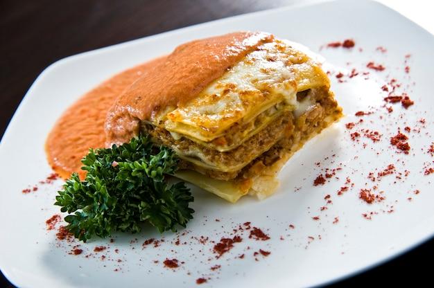 Lasagnes dorées avec viande, tomates, sauce au fromage et pâtes en couches alternées sur une planche de bois garnie de basilic