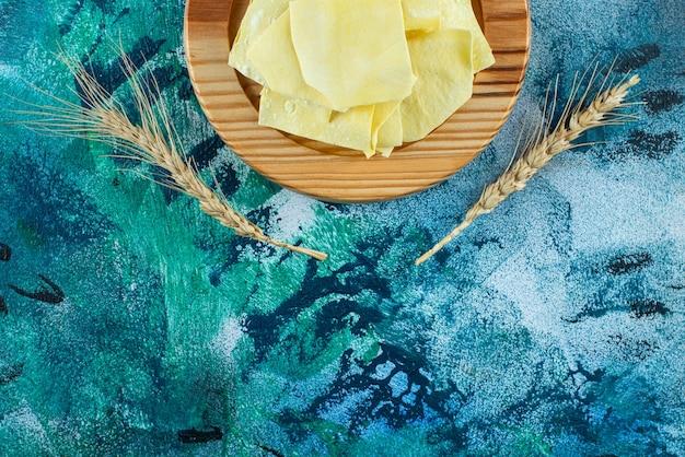 Lasagnes non cuites sur une assiette en bois, sur la table bleue.