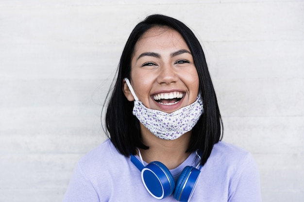 Lating millennial girl smiling devant la caméra tout en portant un masque de protection du visage