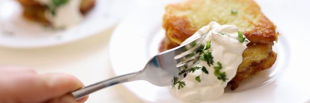 Latke de pomme de terre coupant à la main avec de la crème sure avec des repas en gros plan à la fourchette concept tout compris