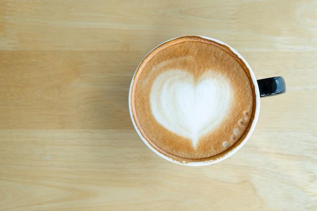 Latte art café dans la matinée avec la lumière du soleil sur le fond en bois de table.