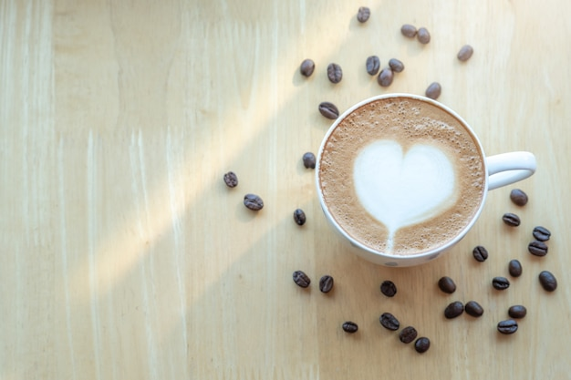 Latte art café et grains de café dans la matinée avec la lumière du soleil