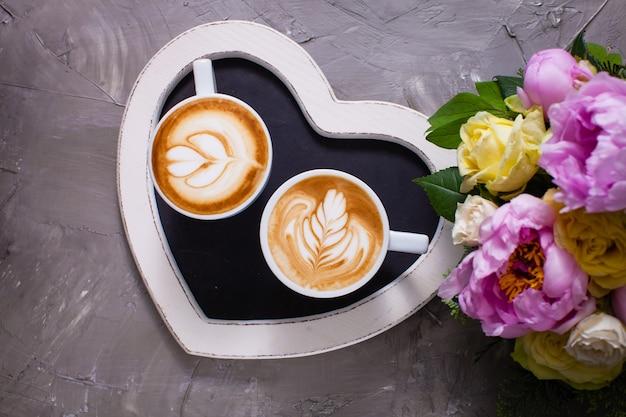 Latte art dans deux tasses de cappuccino sur le plateau en forme de coeur. joyeux matin couple saint valentin