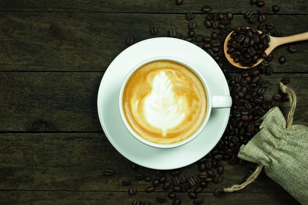 Latte art dans une tasse et grains de café sur une table en bois