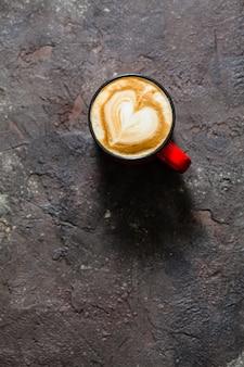 Latte art en forme de coeur dans la tasse de cappuccino. vue de dessus, tasse rouge vintage sur fond texturé béton marron