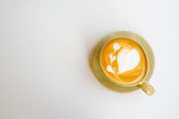 Latte art en tasse sur fond blanc, copie espace et vue de dessus