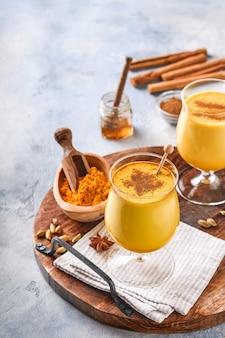 Latte au lait doré au curcuma avec des bâtons de cannelle et du miel. boisson ayurvédique saine. boisson de désintoxication naturelle asiatique à la mode avec des épices pour les végétaliens. espace de copie.