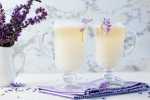 Latte au lait, mousse et lavande dans des verres et un bouquet de fleurs dans une cruche sur une table blanche. café aromatique