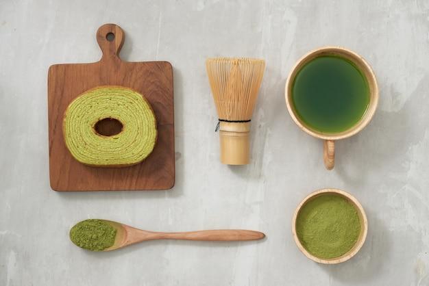 Latte au thé vert matcha dans une tasse et ustensiles de cérémonie du thé avec gâteau allemand. espace de copie