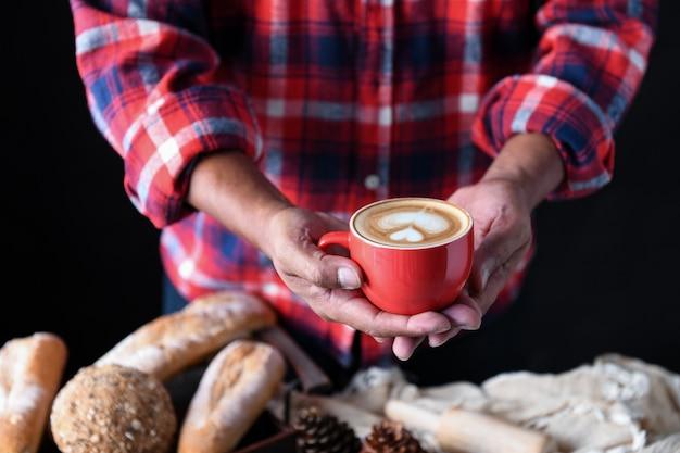 Latte de café de coeur dans la main des jardiniers de barista.