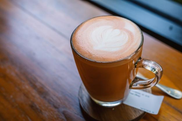 Latte chaud au thé thaï avec mousse de lait latte art en verre