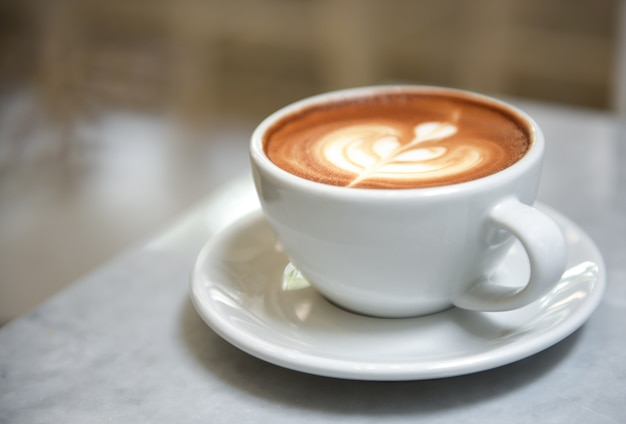 Latte close-up dans une tasse blanche sur la table avec un arrière-plan flou.