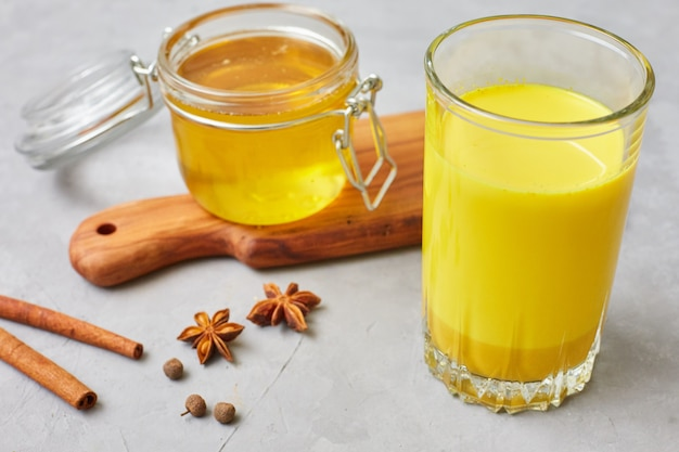 Latte de curcuma avec du lait et des bâtons de cannelle, des étoiles d'anis et du miel. brûleur de graisse dans le foie, immunité accrue, boisson de désintoxication saine anti-inflammatoire