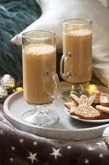 Latte fait maison dans des tasses en verre, servi avec du pain d'épice sur des plaid, des oreillers et des guirlandes.