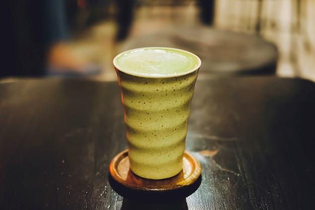 Latte de lait au thé vert matcha chaud avec du lait crémeux dans une tasse en céramique sur la table en bois.