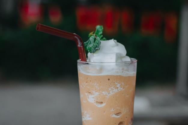 Latte mélangé avec de la crème fouettée, un tracé de détourage. mélangeur à café glacé dans un verre.