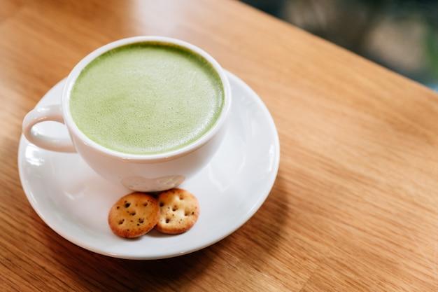 Latte de thé vert chaud et lisse avec de la mousse servie dans une tasse en céramique blanche avec des biscuits