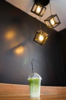 Latte de thé vert glacé sur une table en bois