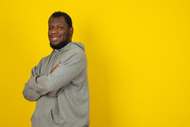 Laughing african american man debout avec les bras croisés, se dresse sur le mur jaune.