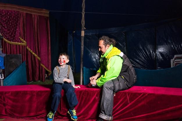 Laughing boy habillé en clown avec maquillage et chemise rayée assis sur scène avec l'homme