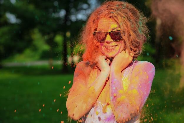 Laughing caucasian woman portant des lunettes couvertes de peinture holi sec