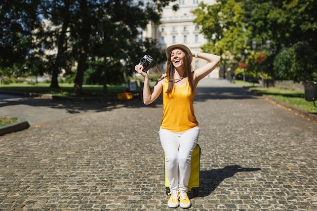 Laughing traveler tourist woman in hat assis sur une valise tenant un appareil photo vintage rétro accroché à la tête en plein air. fille voyageant à l'étranger pour voyager le week-end. mode de vie de voyage touristique.